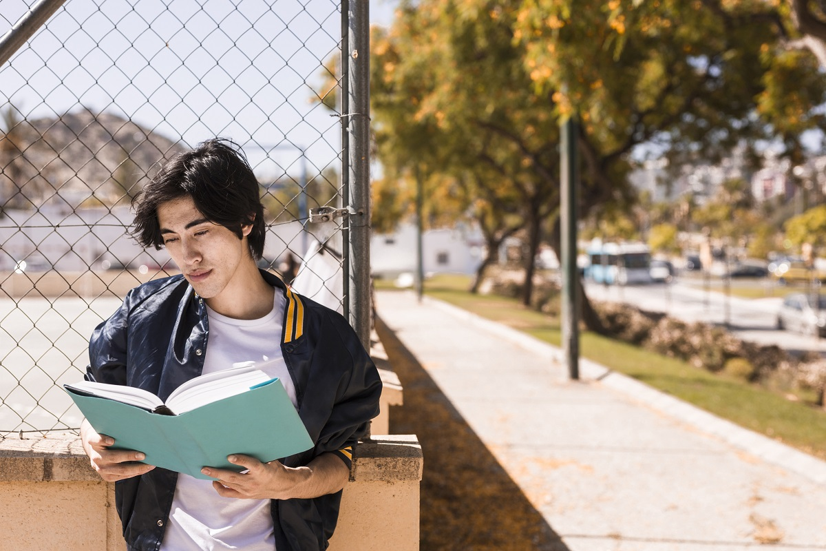 Teen outside reading book