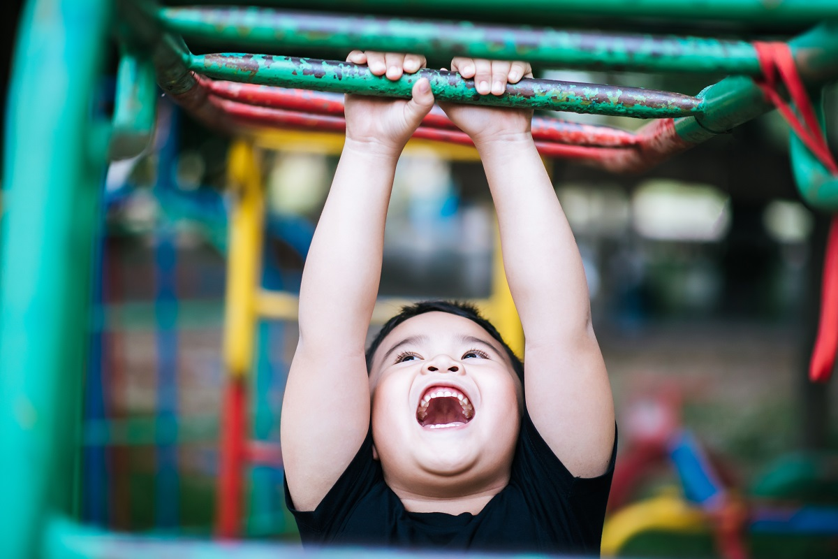 boy hang the bar by his hand in the park
