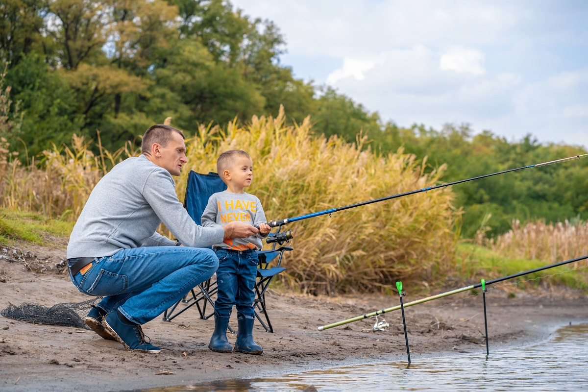 A happy family spends time together they teach their son to fish.