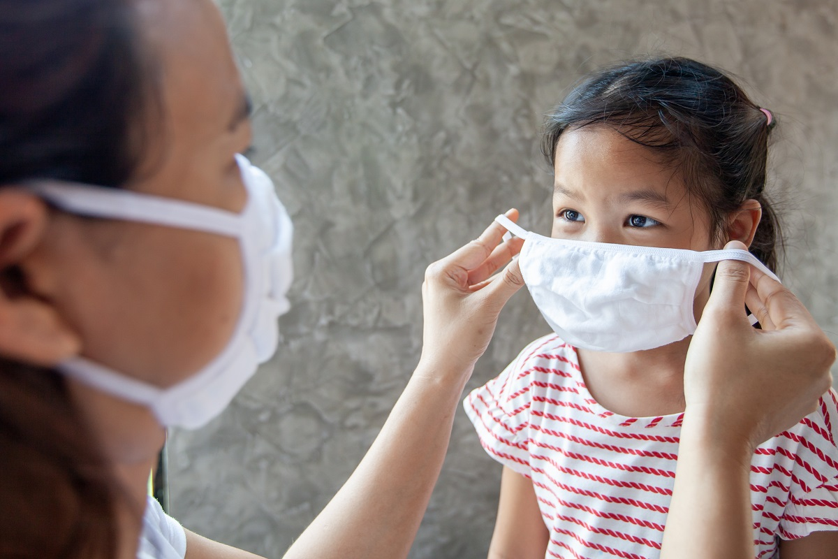 Asian mother help her daughter wearing protection mask to protec